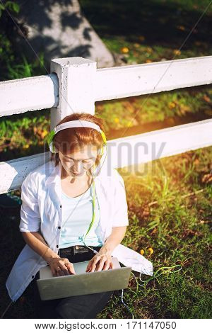 Young women relaxation listening music with notebook sitting on the grass. Outdoor. Sunny day.Greenery tone 2017