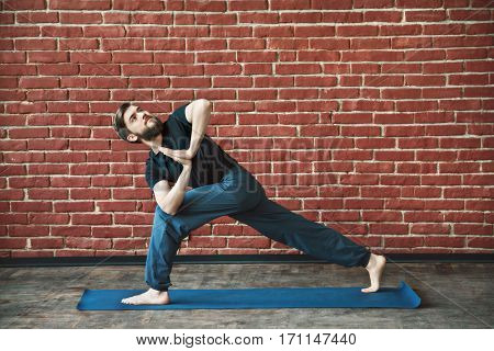 Attractive man with a beard wearing black T-shirt and blue trousers doing yoga position on blue matt at wall background, copy space, parivritta parshvakonasana asana with namaste mudra.