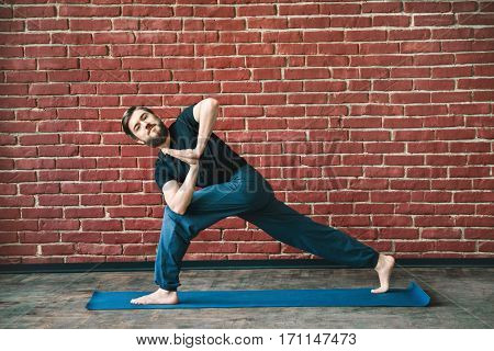 Handsome young man with a beard wearing black T-shirt doing yoga position on blue matt at wall background, copy space, parivritta parshvakonasana asana with namaste mudra.
