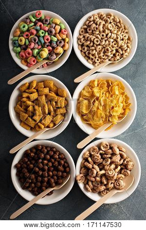 Variety of cold cereals in white bowls with wooden spoons, quick breakfast for kids