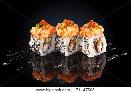 Roll with salmon, shrimp, caviar, cream cheese and spicy sauce on a black background