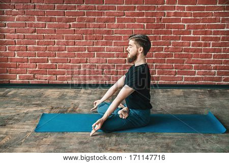 Attractive man with a beard wearing black T-shirt and blue trousers doing yoga position on blue matt at wall background, copy space, lotus asana, padmasana