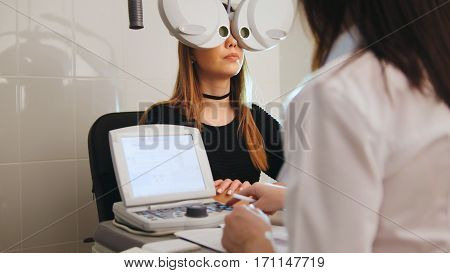 Ophthalmology - eyes clinic concept - optometrist and patient doing exam vision, telephoto