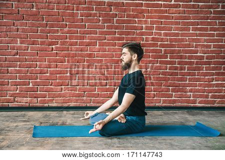 Young bearded man with closed eyes wearing black T-shirt and blue trousers doing yoga position on blue matt at wall background, lotus asana, padmasana, copy space, portrait.