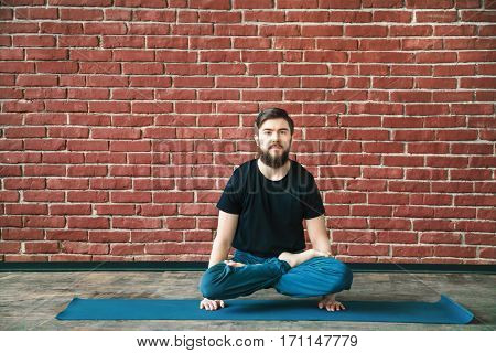 Strong man with a beard wearing black T-shirt and blue trousers doing yoga position padmasana asana on hands on blue matt at wall background, copy space, portrait.