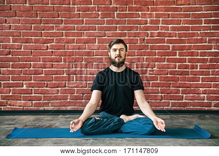 Handsome young man with a beard wearing black T-shirt doing yoga position on blue matt at wall background, copy space, lotus asana, padmasana
