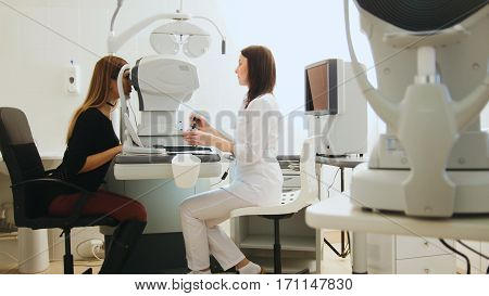 Optician with tonometer and patient at eye clinic, diagnostic, horizontal