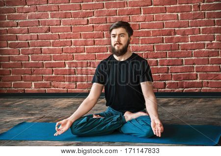 Darkhaired man with a beard wearing black T-shirt and blue trousers doing yoga position on blue matt at wall background, copy space, portrait, lotus asana, padmasana