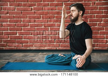 Handsome young man with a beard wearing black T-shirt doing yoga position on blue matt at wall background, copy space, portrait, pranayama exercises.