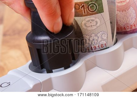 Hand Of Woman Turns Off Electrical Plug, Polish Currency Money, Energy Costs