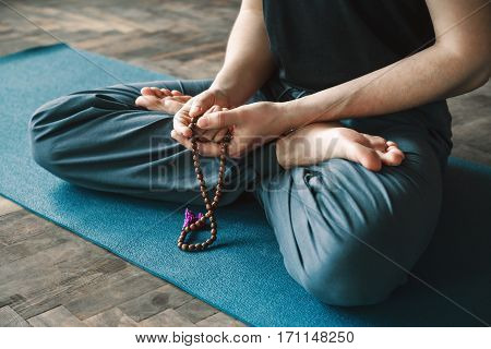 A portrait of man's hands holding string and sitting in lotus asana, yoga position, copy space.