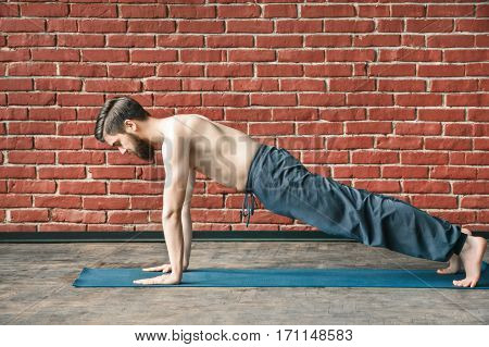 Fit young man with a beard wearing trousers doing yoga position on blue matt at wall background, copy space, portrait, plank.