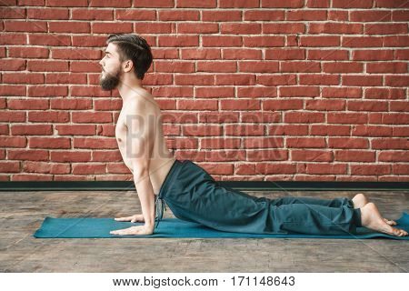 Young man with dark hair and beard wearing trousers doing yoga position on blue matt at wall background, copy space, portrait, cobra pose bhujangasana asana.