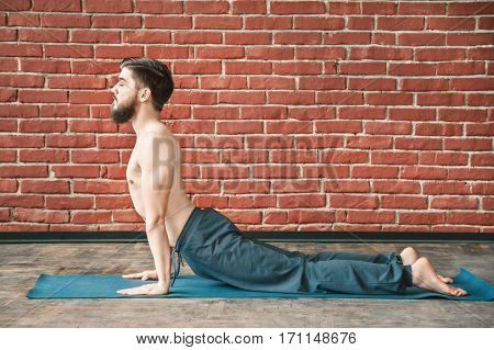 Handsome man with dark hair and beard wearing trousers doing yoga position, closed eyes,  on blue matt at wall background, copy space, portrait, closed eyes, cobra pose bhujangasana asana.