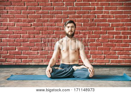 A portrait of young man with dark hair and beard wearing trousers doing yoga lotus position and sitting on blue matt at wall background, copy space, portrait.