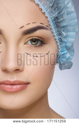 Dashed lines around eyes of girl. Beautiful girl in protective cap. Plastic surgery, beauty portrait, half face, closeup