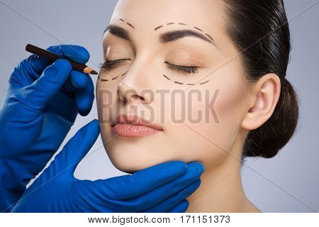 Plastic surgeon drawing dashed lines around closed eyes of girl. Hands in blue glove holding pencil and face. Face turned aside. Plastic surgery, beauty portrait, closeup
