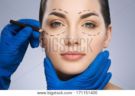 Plastic surgeon drawing dashed lines around eyes of girl, under her eye. Hands in blue glove holding pencil and face. Plastic surgery, beauty portrait, closeup