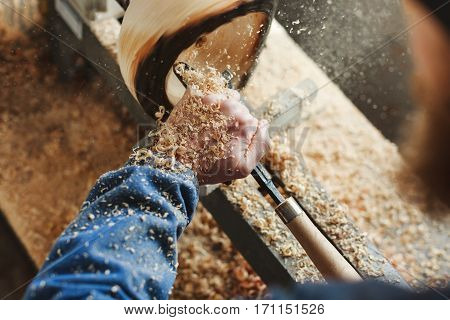 Worker's hands in  blue jeans suit working with woodcarving machine, instruments and wood, shavings on table, close up, woodworking, copy space.