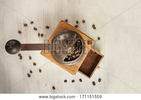 An overhead photo of a vintage coffee grinder, shot against the background of light wooden boards texture, with coffee grains and copy space