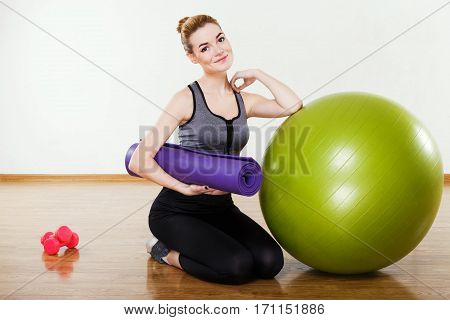 Young girl with light brown hair wearing black snickers, leggings and dark short top sitting with fitball and pink dumbbells at gym, fitness, holding gym mat.