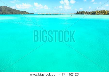 Stunning view of blue turquoise lagoon and far bungalows on background of Bora Bora island French Polynesia