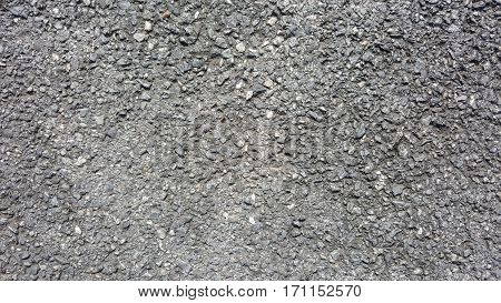 Fragment of the road surface with small stones and bitumen. Close-up