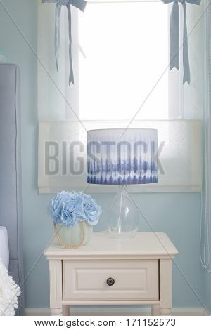 Flower Jar And Reading Lamp On Bedside Table In Light Blue Interior Bedroom
