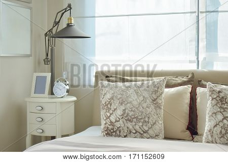 Luxury Bedroom With Lamp And Alarm Clock On Wooden Table At Home