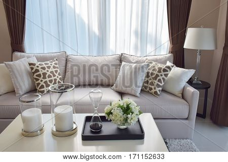 Modern Living Room With Sandglass, Flower And Row Of Pillows On Sofa