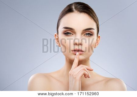 Beautiful model with big blue eyes and perfect make-up looking at camera. Finger touching lower lip. Beauty portrait, head and shoulders, studio, indoor