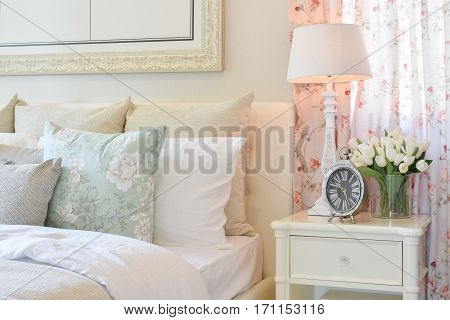 Vintage Bedroom Interior With Decorative Table Lamp, Alarm Clock And Flower On White Table