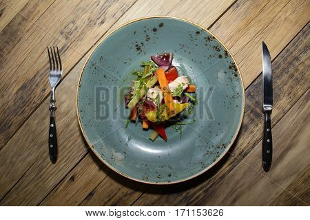 Italian salad on the woden table with knive and fork
