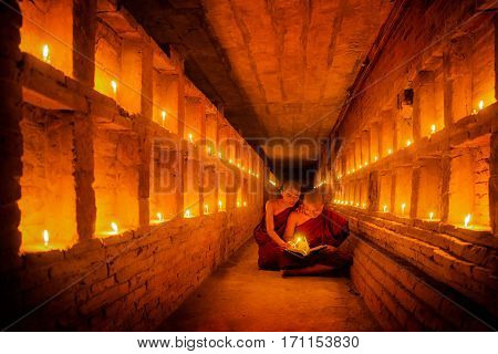 Young Buddhist Monk are reading a book with light from candle and sun light from outside to inside pagoda of old bagan with statue in mandalay historical park mandalay myanmar