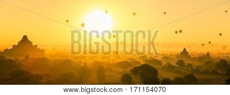 Hot air balloon over plain and pagoda of Bagan in misty morning Myanmar