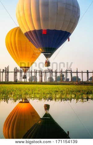 Sunrise at U Bein Bridge with boat and hot air balloon Mandalay Myanmar.