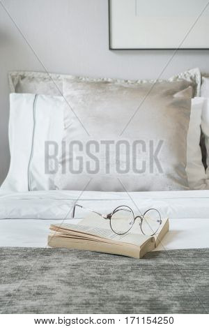 Glassed And Book On Bed With Velvet Finished Pillows On Background