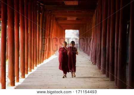 Young Buddhist monk novic walking and reading in pagoda in Shin Bin Maha Laba Man Temple Sa layBagan near Mandalay city Myanmar.