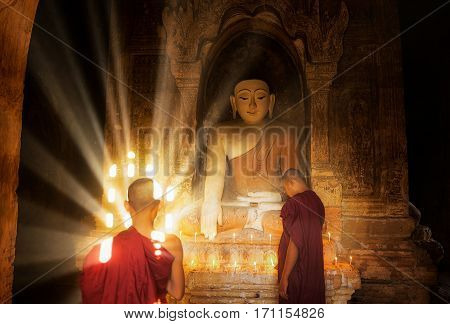 Young Buddhist Monk are reading with sun light from outside to inside pagoda of old bagan with statue in mandalay historical park mandalay myanmar