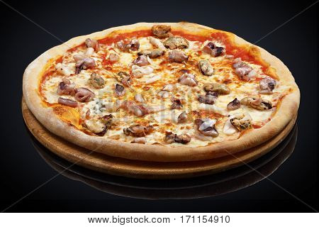 Seafood pizza with squid, shrimp, mussels on a black background