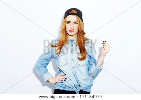 Young teenage red-haired girl with long hair wearing blue shirt and black hat, red lips, black manicure, copy space, confused posing, portrait.