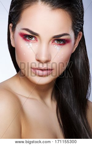 Girl with bright make-up looking at camera. Eyelids colored in red with little glittering stars. Loose hair on shoulder. Beauty portrait, head and shoulders, closeup, studio