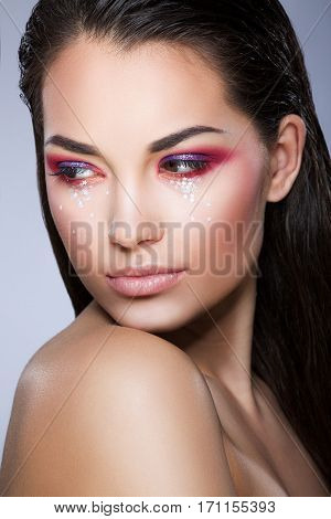 Girl with bright make-up looking aside. Eyelids colored in red and purple with little glittering stars. Loose hair. Beauty portrait, head and shoulders, studio