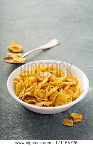Cornflake cereals in a bowl with spoon on blue background, quick breakfast