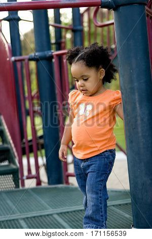 Cute little biracial girl playing at the park.