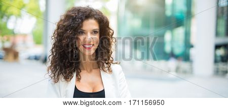 Smiling woman walking in a city, Wide image