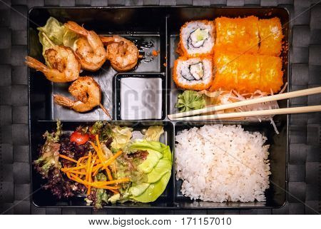 Bento box with salad, maki, shrimps and rice