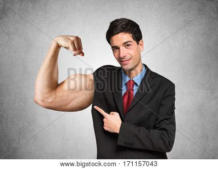 Powerful businessman showing his biceps
