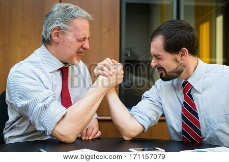 Business people doing arm wrestling in their office. Shallow depth of field, focus on the man on the right