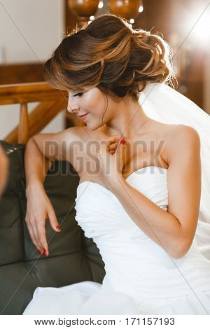 Pre-wedding preparation. Fiancee sitting on sofa. Bride wearing white wedding dress and veil. Indoor, profile
